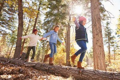 Kinder balancieren auf einem Baumstamm