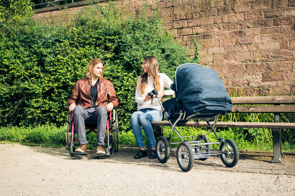 Junges Paar im Park, der Vater im Rollstuhl, die Mutter mit Kinderwagen